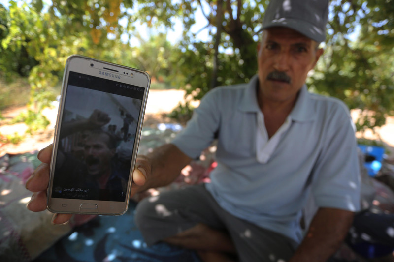 Man sitting on ground in vineyard shows photo on his phone