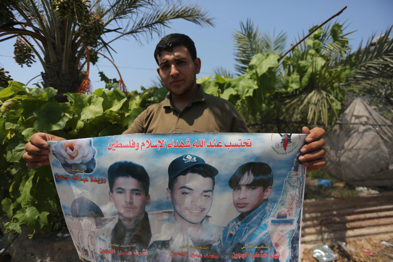 Man, seen from chest up, holds poster showing images of three youths and a rose representing slain woman