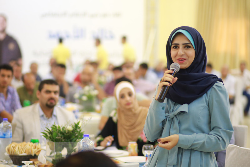 Young woman seen from waist up speaks into a microphone in a banquet hall