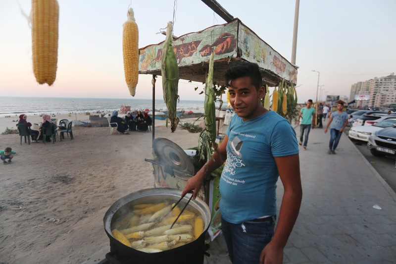 Teenager seen from waist up cooks corn in a vat in front of a stand on Gaza's corniche