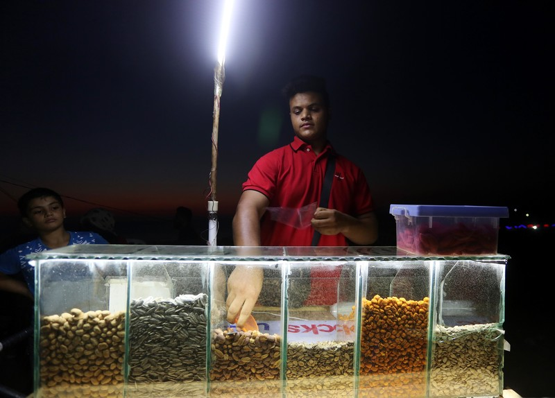Young man seen from waist up scoops nuts at outdoor booth at nighttime