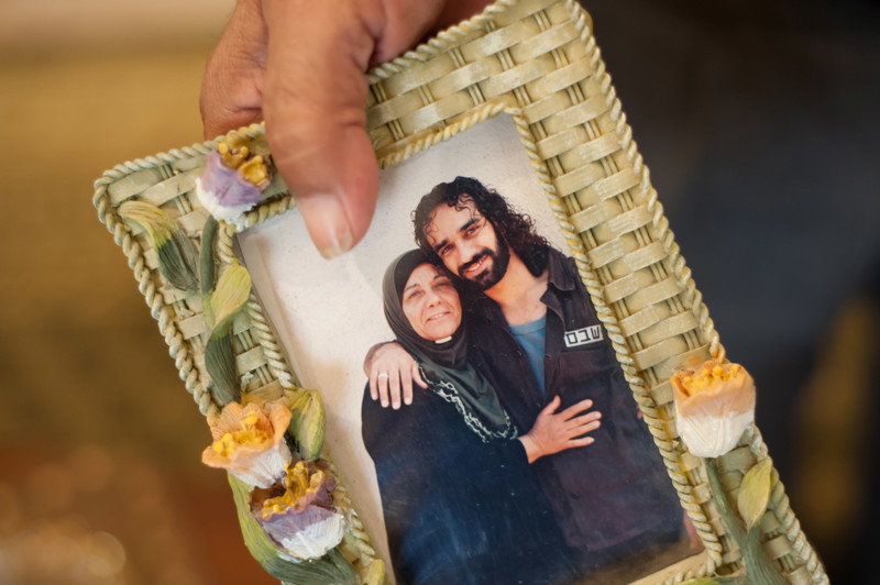Photo shows hand holding framed photograph of older woman embracing younger son wearing prison uniform
