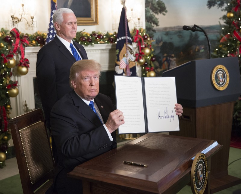 Trump sits at desk holding up newly signed executive order as Vice President Pence stands behind him