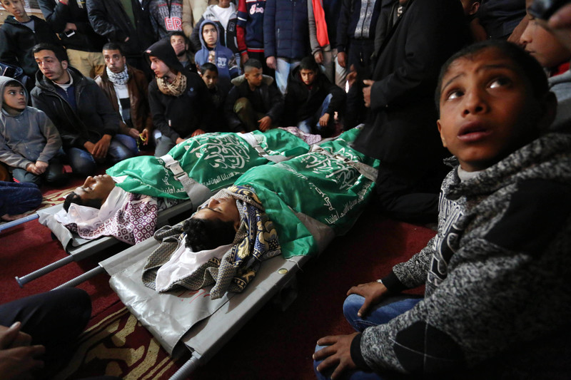 The shrouded bodies of two boys, wrapped in green flags, lay on stretchers while surrounded by mourners