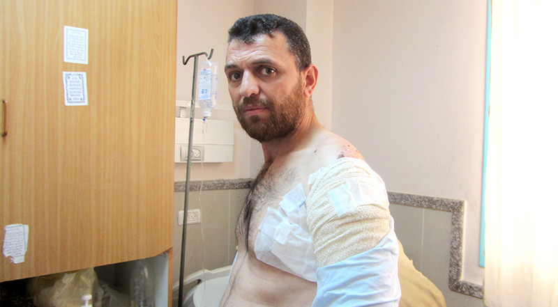 Man with bandages on his upper arm and chest sits in hospital room
