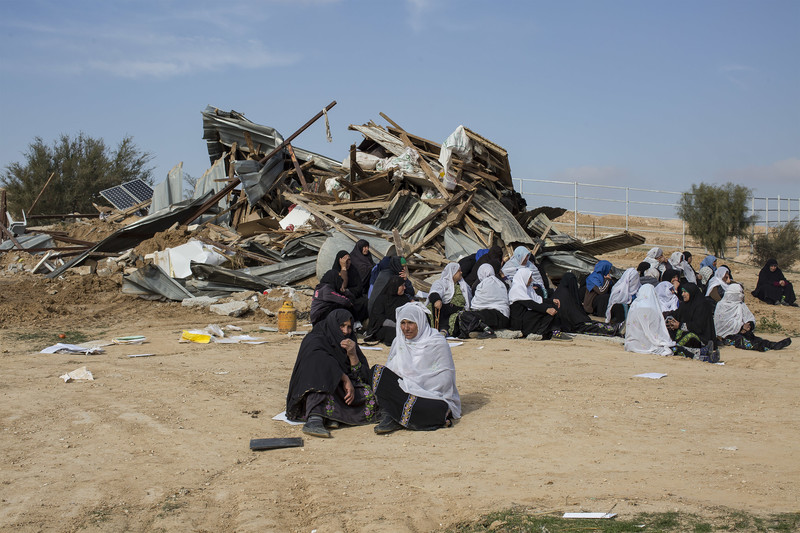 Several women sit in front of pile of debris