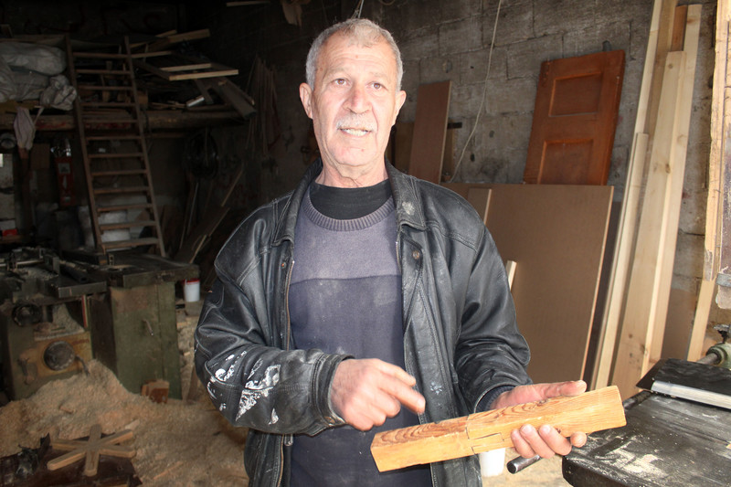 Man wearing leather jacket points to a piece of wood he is holding