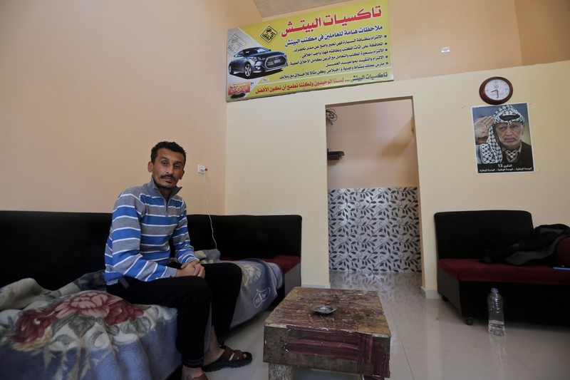 Young man sits on couch in sparely furnished room with a poster of Yasser Arafat on the wall