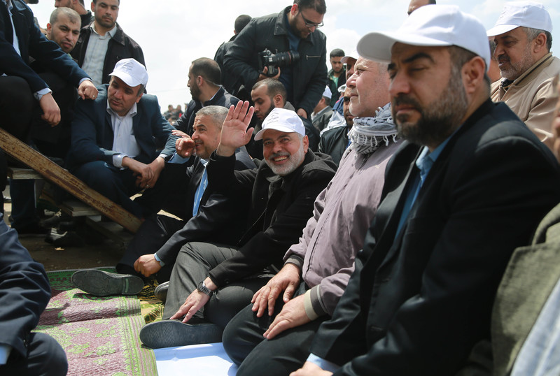 Ismail Haniyeh, wearing white baseball cap, sits on ground and waves towards camera