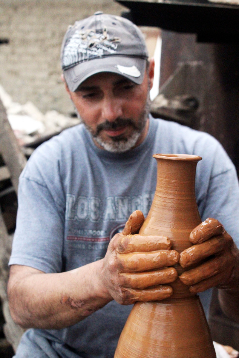 Man wearing baseball cap shapes a wet clay vase with his hands