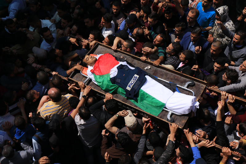 Crowd carries body of man shrouded in Palestinian flag with flak jacket marked PRESS laid on his body