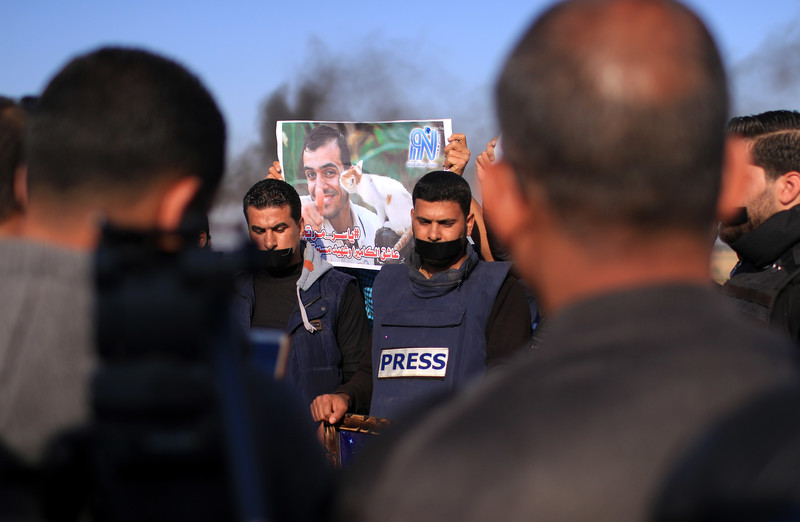 Protesters wearing flak jackets display poster of Yaser Murtaja holding a kitten