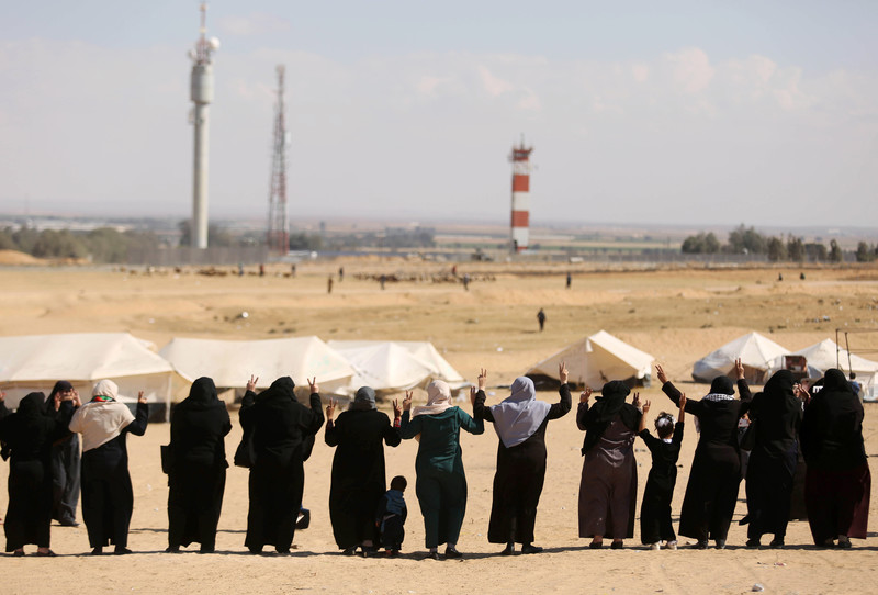 Photo shows backs of women standing in a row making V for victory signs with their hands near the Gaza-Israel boundary fence
