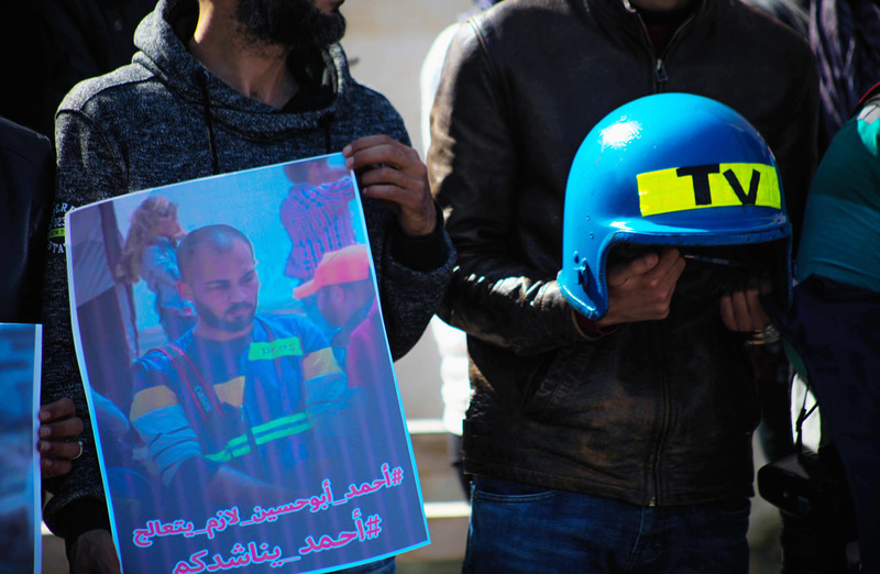 Protesters hold up a poster of Ahmad Abu Hussein and a blue helmet