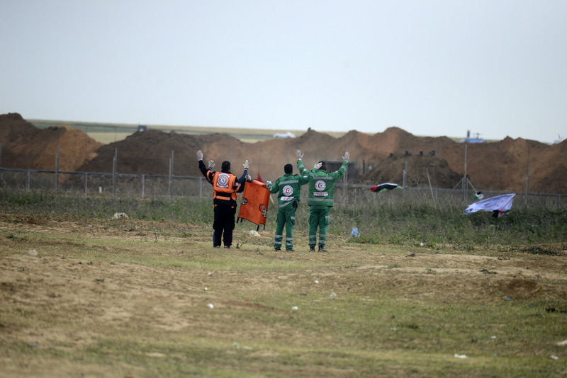 Three medics carrying a folded up stretcher put their arms in the air in front of Gaza-Israel boundary fence