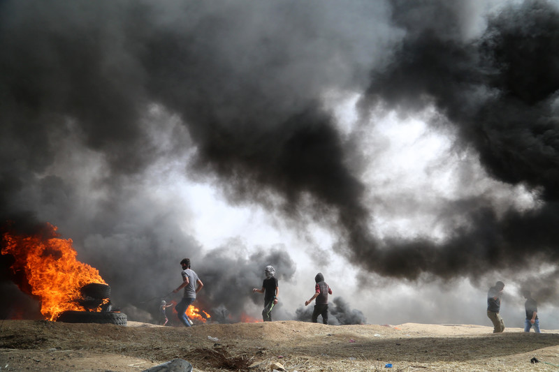 Landscape view of protesters against thick plumes of smoke from burning tires