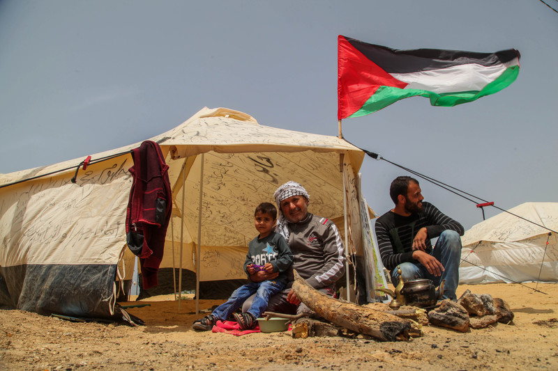 Two men and a small boy sit outside of a cloth tent with a Palestinian flag raised above it