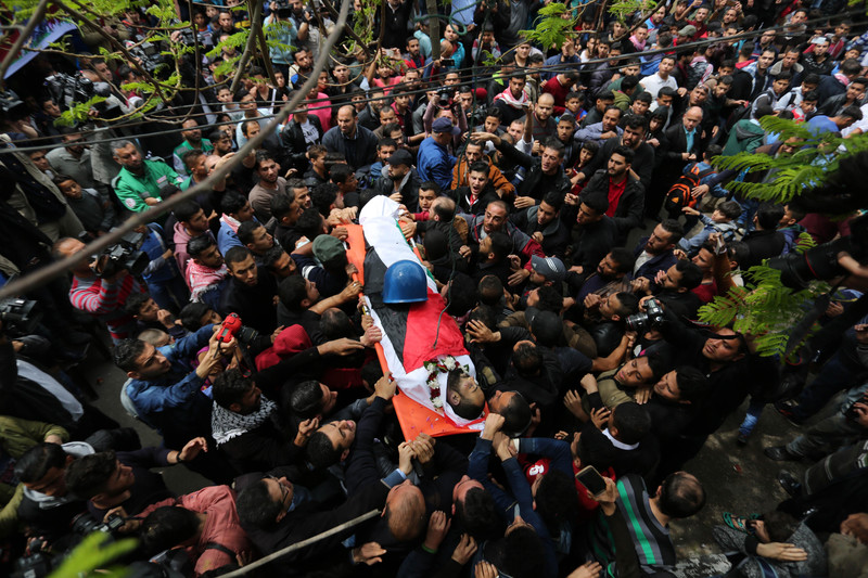Body of journalist, wrapped in a Palestinian flag, is carried by a crowd of people with his protective helmet resting on him