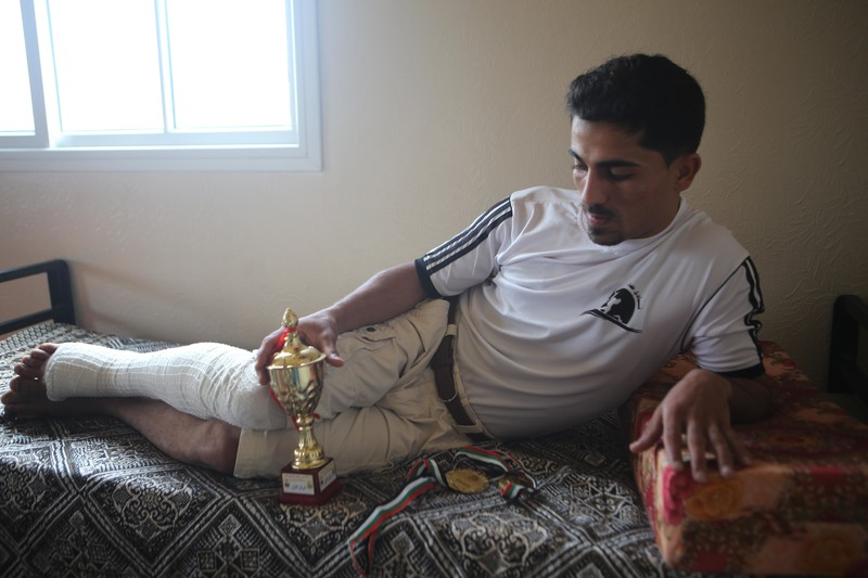 Young man with bandaged leg holds a trophy as he lies across a bed in a sparely furnished room