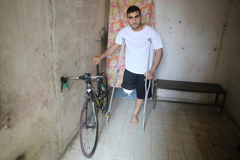 Man with amputated leg uses a crutch with one arm while holding on to the seat of his bicycle with his other arm