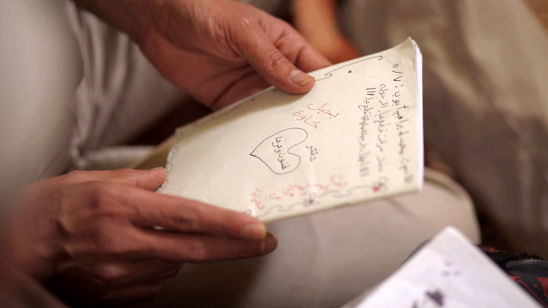 Photo shows two hands holding a notebook with Arabic handwriting on it