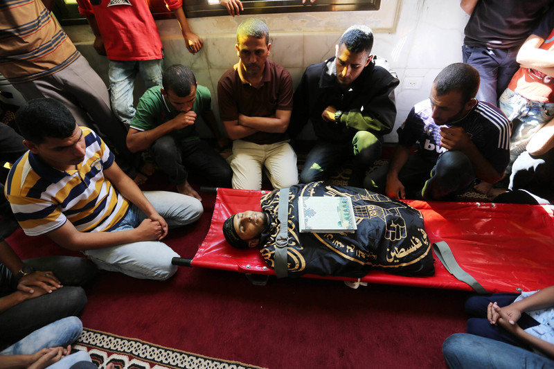 Men sit around the body of a young man wrapped in the flag of the Islamic Jihad faction, lying on a stretcher with a book placed on his chest