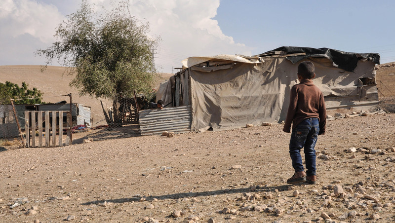 A small child stands in front of a structure made of corrugated sheets and tarps
