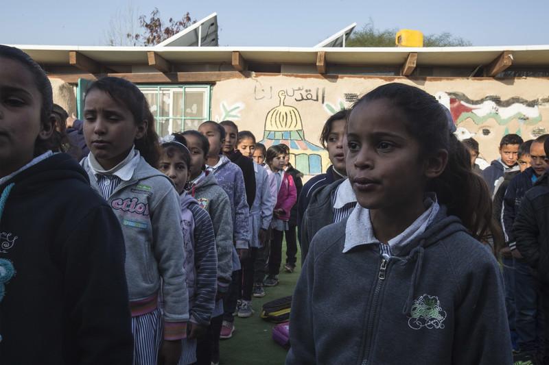 Schoolchildren stand in rows in front of single-story school