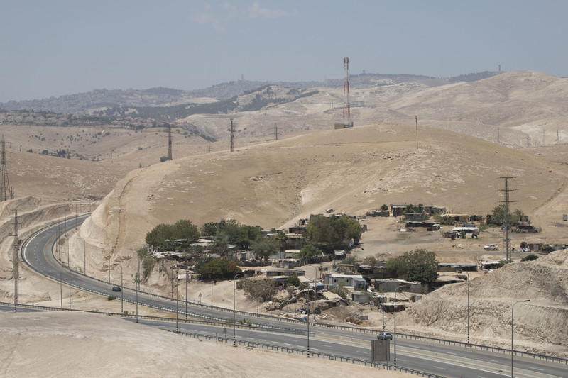 Landscape view of ramshackle village surrounded by fenced road and barren hills
