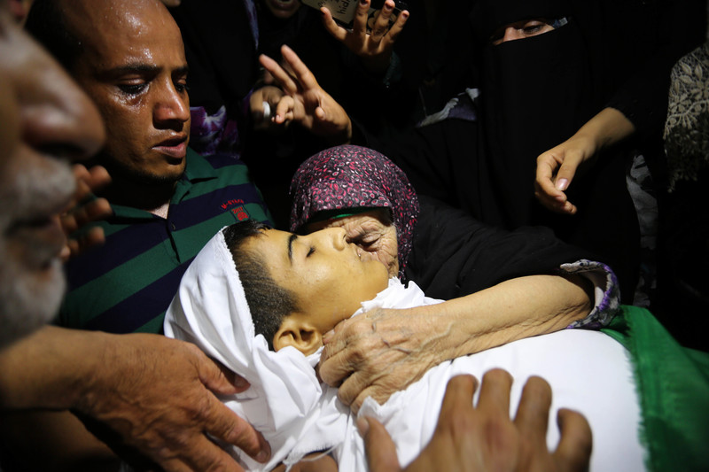 Mourning people surround and place their hands on the shrouded body of slain child