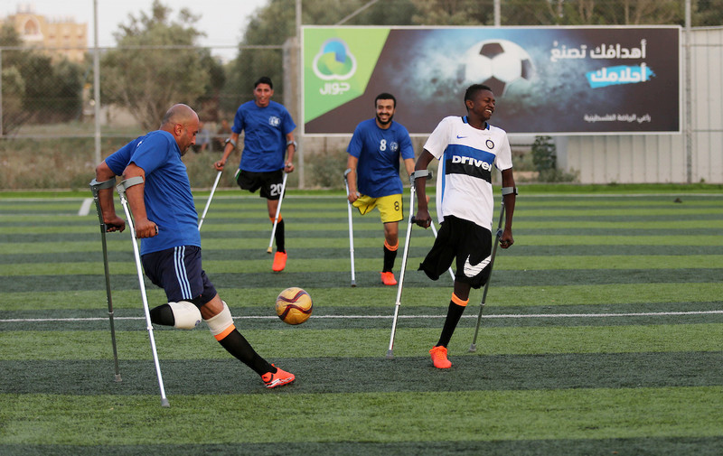 Photo shows four players using crutches competing for control of a ball on a football pitch