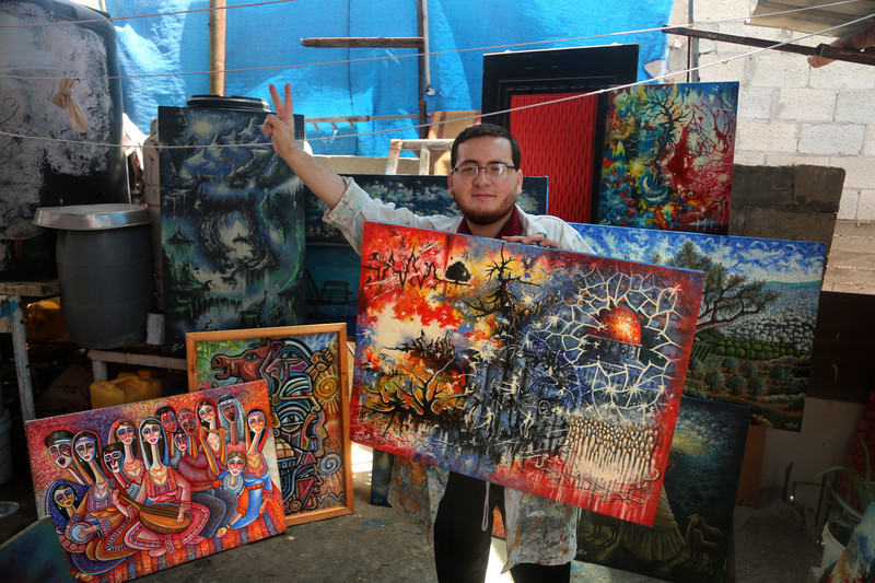 Young man holding large painted canvas gives the victory hand gesture as he stands in a room surrounded by his paintings