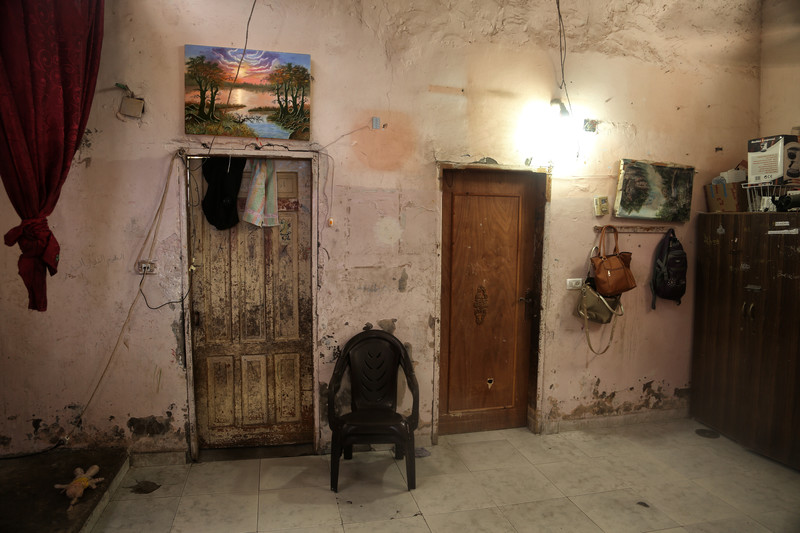 Two colorful landscape paintings hang above door frames in a sparely furnished room