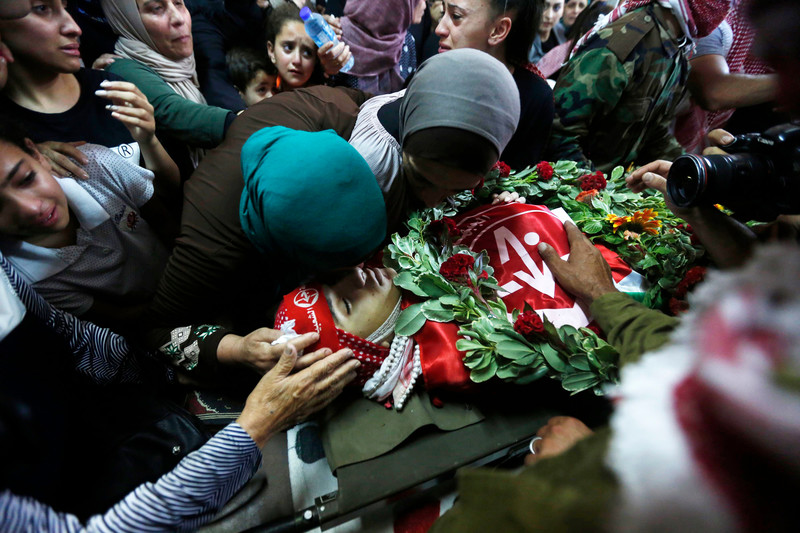 Women and girls mourn over body of youth wrapped in PFLP flags with a wreath placed on his torso