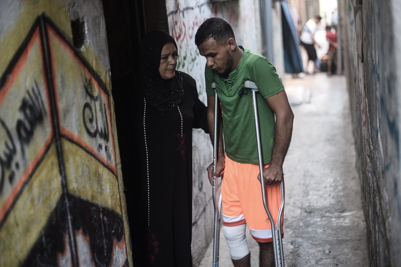 Laila puts her hand on the back of her son Ahmad as he stands using crutches in an alley