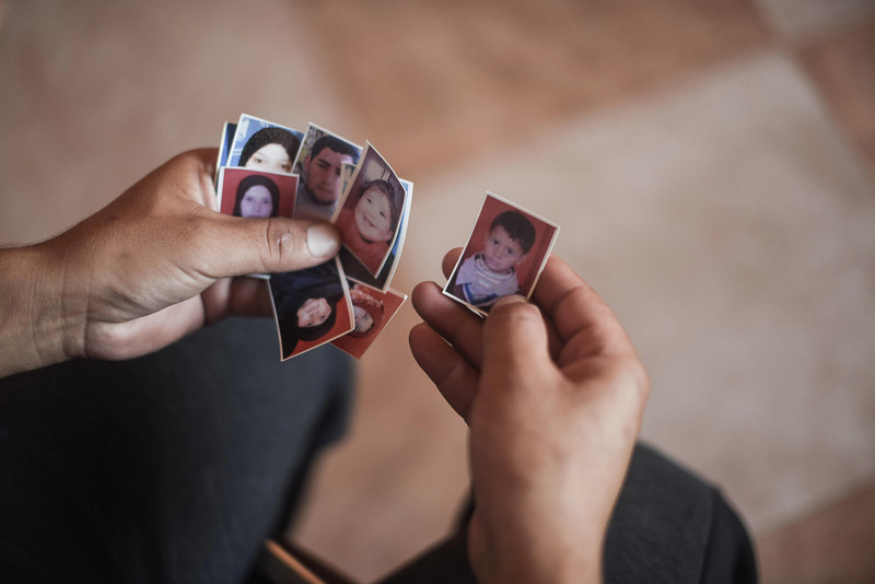 Close-up of two hands holding passport-sized portrait photos