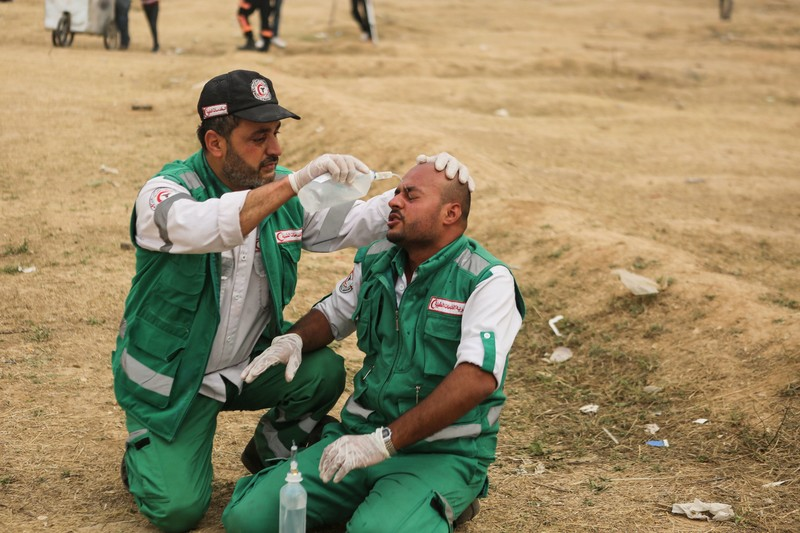 Adel al-Masharawi, kneeling on the ground while wearing paramedic uniform, pours liquid onto face of another paramedic sitting on the ground
