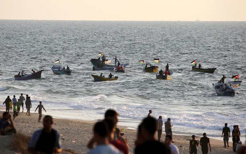 People stand on the beach with boats with Palestinian flags on the water in the background