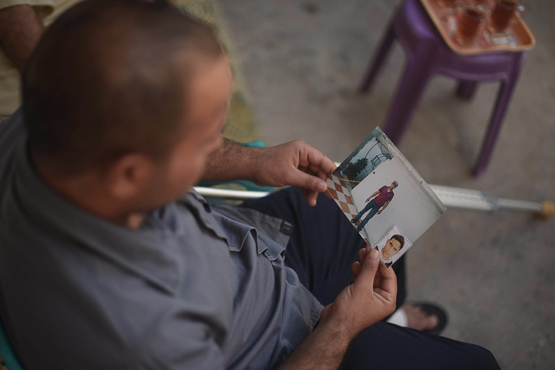 Photo taken from above shows sitting man looking at two photographs he is holding