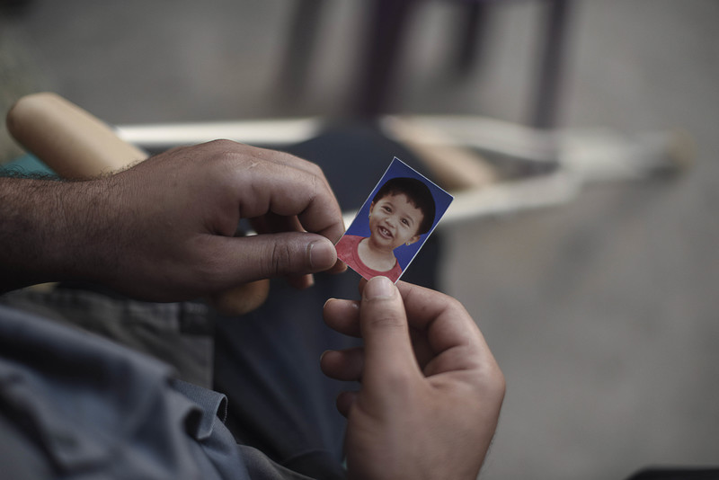 Close-up photo of two hands holding a passport-size image of a smiling baby