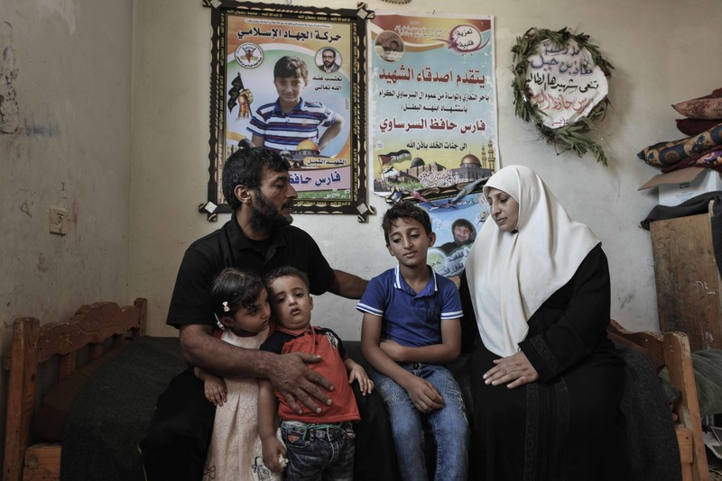 A woman and man sit on a twin-sized bed with three children and posters honoring their slain son on the wall behind them