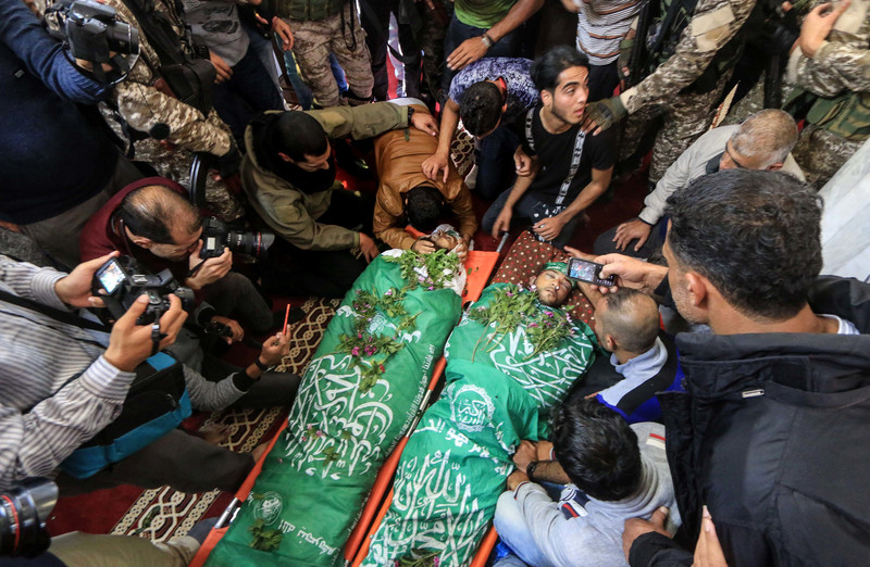 A crowd surrounds the bodies of two young men wrapped in Hamas flags and covered with flowers