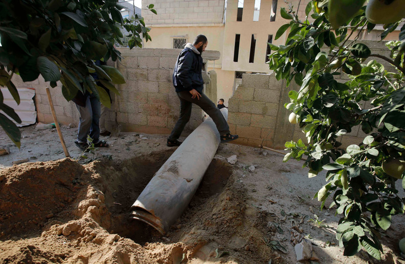 A Palestinian man steps over an unexploded missile around two meters long