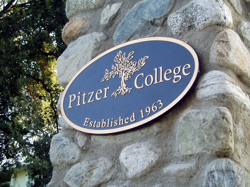 "A metal placard on a stone wall says ""Pitzer College, established 1963."""