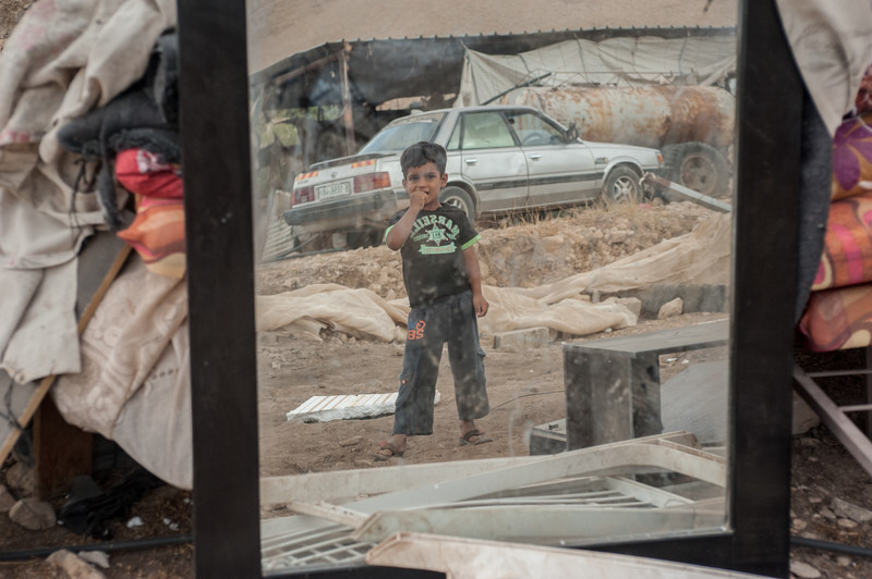 A child is seen in the mirror of a car playing in the rubble of a demolished building.