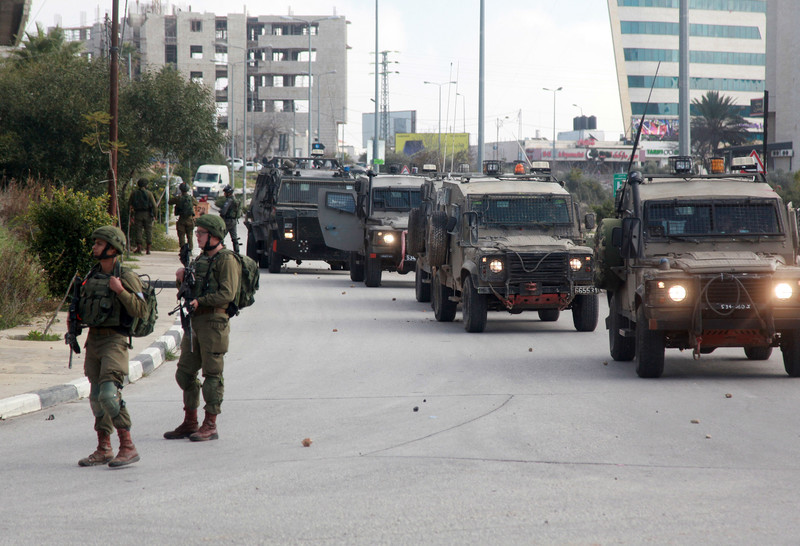 Israeli soldiers stand near four jeeps on road littered with stones