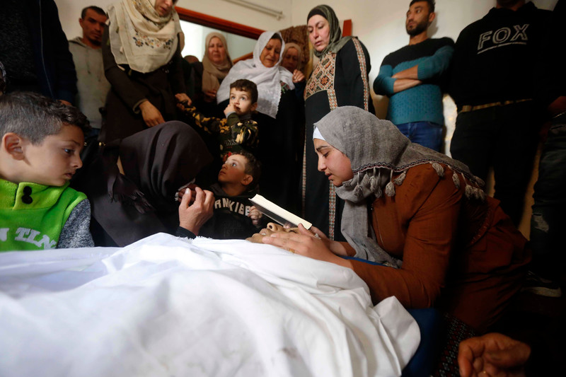 A girl holding a book cradles the face of a shrouded dead man as men, women and children stand nearby