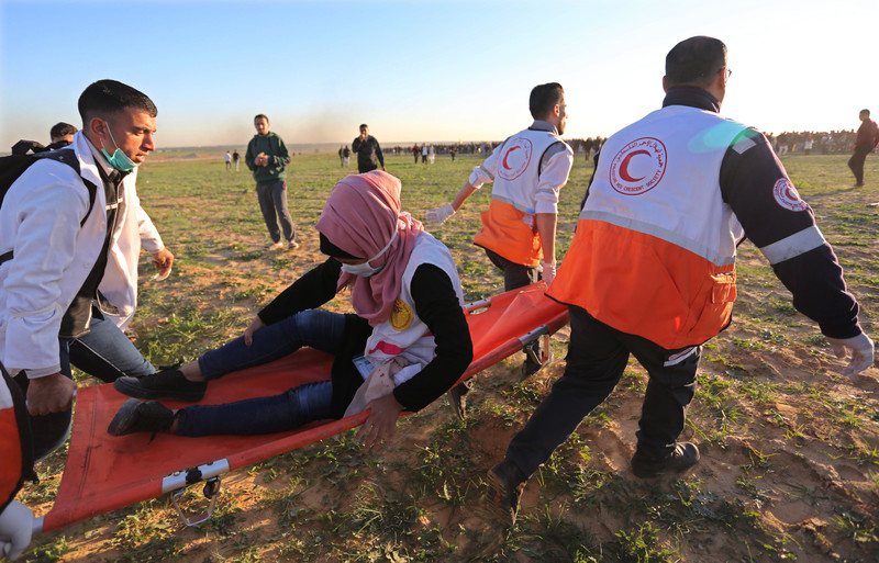 A woman grips her leg while being carried on a stretcher by three paramedics