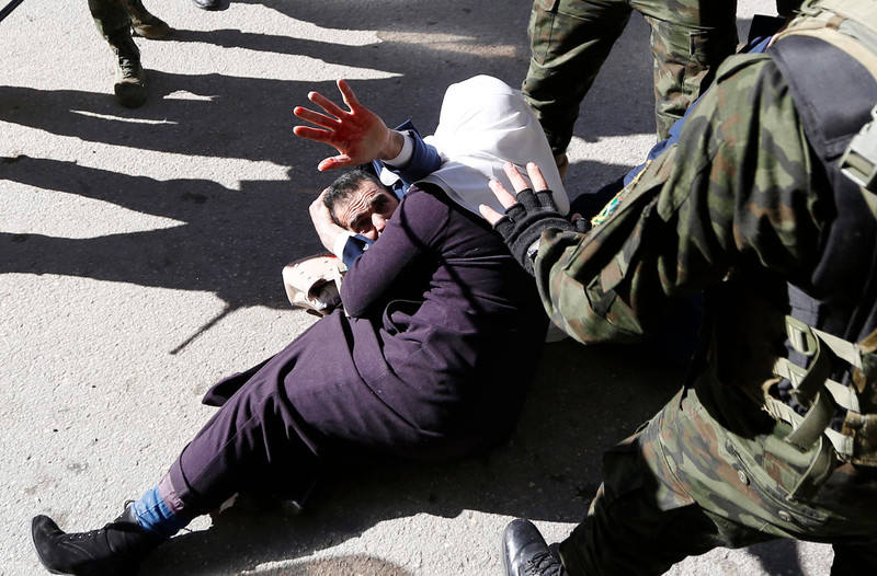Man lying on ground uses one hand to cover his head and raises his other hand, covered in blood, in the air as a woman lies across him as men in military uniform stand beside them