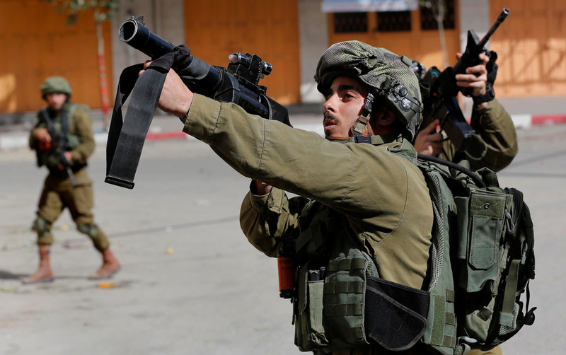 Two Israeli soldiers point their weapons at Palestinian demonstrators.